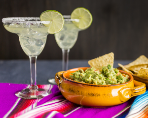 Green Chile & Tequila Guacamole served with fresh corn tortilla chips in a beautiful yellow ceramic bowl and two salted margaritas on the rocks.