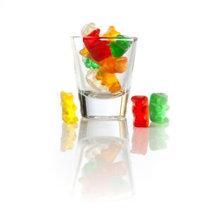 A clear shot glass filled with red, yellow, green, white, and orange gummy bears.
